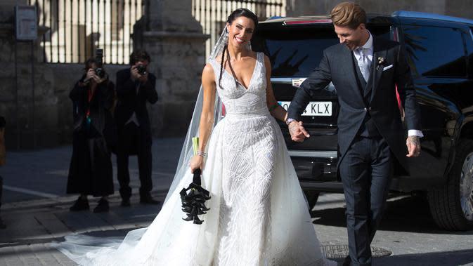 Bek Real Madrid, Sergio Ramos menggenggam tangan istrinya, Pilar Rubio setelah upacara pernikahan mereka di Sevilla, Spanyol (15/6/2019). Ramos resmi menikahi kekasihnya Pilar Rubio setelah berpacaran sejak 2012. (AP Photo/Antonio Pizarro)