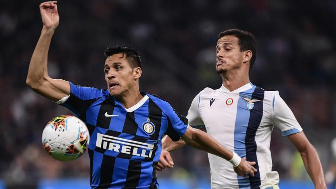 Penyerang Inter Milan, Alexis Sanchez (kiri) berusaha mengontrol bola dari kawalan bek Lazio, Luiz Felipe pada pertandingan lanjutan Liga Serie A di stadion San Siro, Milan (25/9/2019). Inter Milan menang tipis atas Lazio 1-0 berkat gol Danilo D'Ambrosio. (AFP Photo/Marco Bertorello)