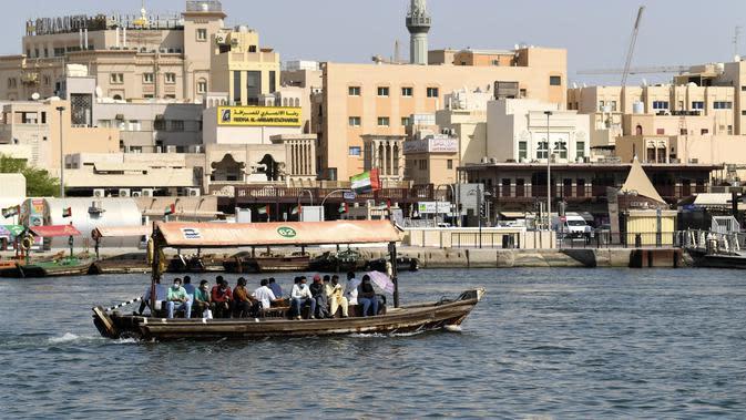 Orang-orang naik perahu di atas kapal kayu tradisional di dekat Deira Souk di Teluk Emirat Dubai (30/9/2020). (AFP/Karim Sahib)