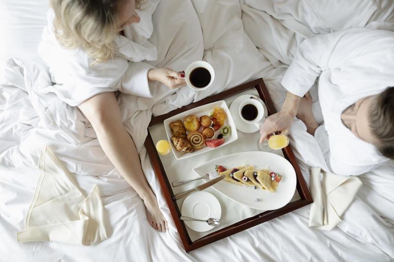 Couple in bathrobes enjoying breakfast in bed in luxury hotel, enjoying romantic weekend
