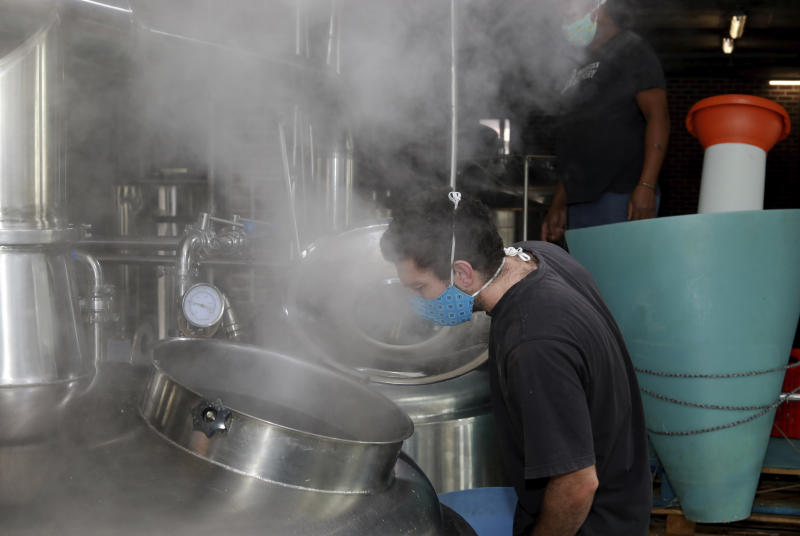 In this Friday, May 15, 2020, photo, a brewer wearing a face mask checks vegetable soup being cooked at Woodstock Brewery in Cape Town, South Africa. During the coronavirus lockdown, South Africa is restricting the sale of cigarettes and alcohol. The brewery has adapted to the ban by using its large vats to cook meals for the city's poor. (AP Photo/Nardus Engelbrecht)