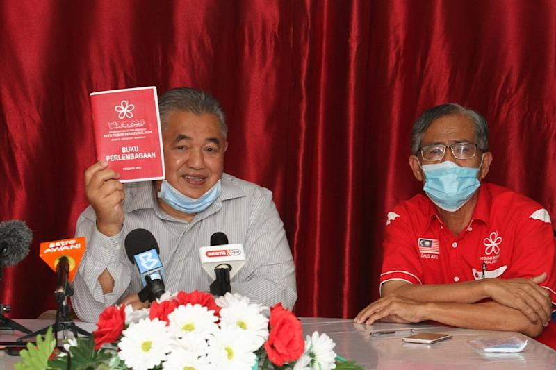 Johor Bersatu deputy chief Md Nasir Hashim (left) shows the party's constitution book as Bersatu Johor Baru division chief Zais Mohd Akil looks on during the press conference in Johor Bari May 29, 2020. — Picture by Ben Tan