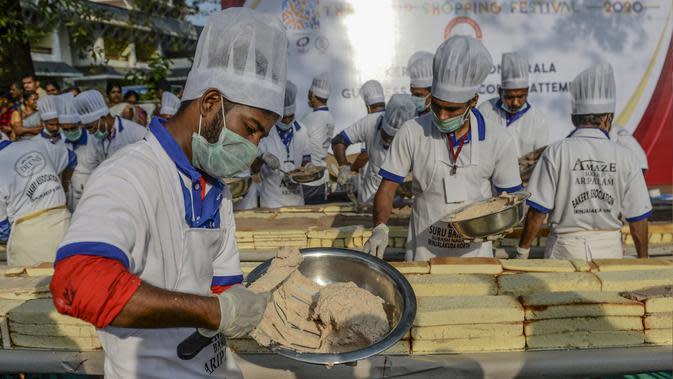 Pembuat roti dan koki menyiapkan kue sepanjang 6,5 km untuk kue terpanjang dunia, di Thrissur di negara bagian Kerala, India selatan (15/1/2020). Sebelumnya rekor Guinness World Record untuk kue terpanjang diraih di China degan panjang 3,2 kilometer. (AFP/Arun Sankar)