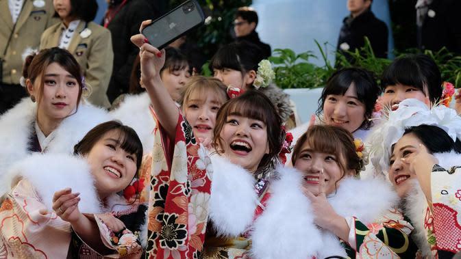 Sejumlah gadis Jepang mengenakan kimono berkumpul untuk upacara Coming of Age Day atau Hari Kedewasaan di Tokyo Disneyland, di Urayasu, Senin (13/1/2020). Coming of Age Day atau Hari Kedewasaan ini menandakan diperbolehkannya merokok, mengonsumsi alkohol dan mengikuti Pemilu. (Kazuhiro NOGI/AFP)