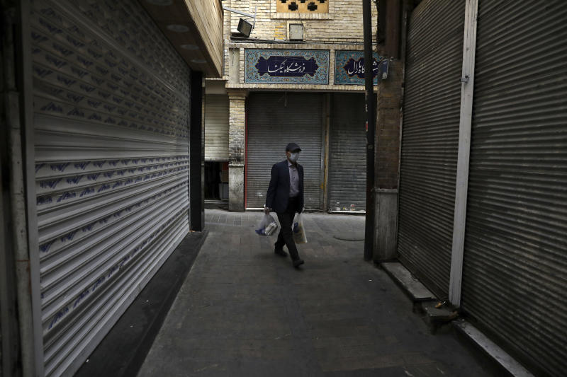 A man wearing a face mask and gloves to protect against the new coronavirus carries his shopping as he walks past closed shops at the Tajrish traditional bazaar in northern Tehran, Iran, Saturday, April 4, 2020. In the first working day after Iranian New Year holidays authorities have allowed some government offices and businesses to re-open with limited working hours, when schools, universities, and many businesses still are ordered to be closed aimed to prevent the spread of the virus.  (AP Photo/Vahid Salemi)