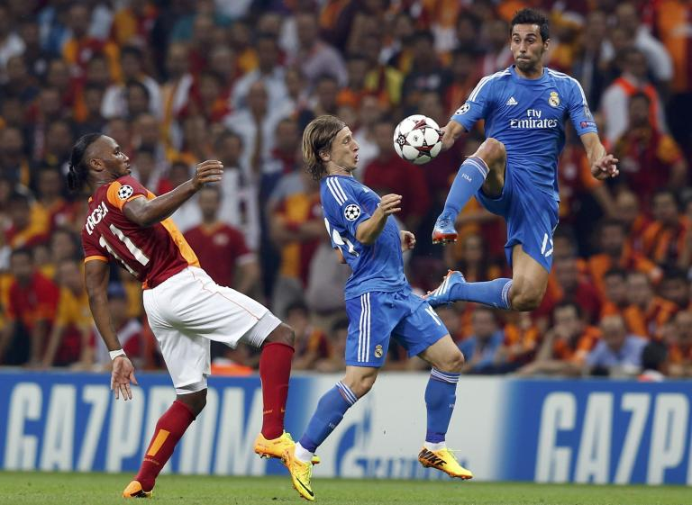 Galatasaray's Drogba challenges Real Madrid's Modric and Arbeloa during their Champions League soccer match in Istanbul