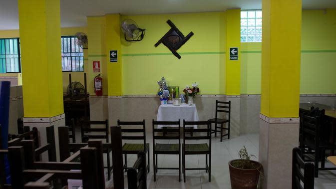 Altar untuk menghormati Wilfredo Davila Minano - korban COVID-19 - terlihat di restoran ceviche yang dimilikinya (saat ini tutup) di Trujillo, Peru, 23 Juni 2020. Hingga 25 September 2020, kematian global akibat COVID-19 hampir mencapai satu juta, sepertiganya di Amerika Latin. (Celso Roldan/AFP)