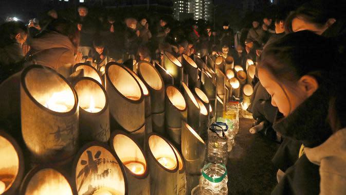 Orang-orang berdoa untuk para korban di sekitar lilin untuk memperingati 25 tahun gempa Hanshin Besar di sebuah taman di Kobe, Prefektur Hyogo (17/1/2020). Lebih dari 6.400 orang tewas dalam gempa bumi dahsyat yang melanda daerah Kobe pada 1995. (AFP/Jiji Press/AFP)