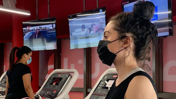 Seorang wanita mengenakan masker berlatih di sebuah gym di Riyadh, Arab Saudi (23/6/2020). Pemerintah Arab Saudi mulai membuka kembali kegiatan perekonomian setelah melonggarkan lockdown Covid-19. (AFP Photo/Rania Sanjar)