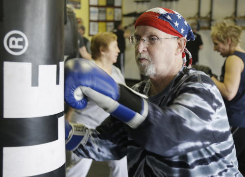 In this photo taken March 19, 2013, Dave Beery hits a heavy bag during a workout at Rock Steady Boxing in Indianapolis. Rock Steady boxing is a unique nonprofit gym that, since 2006, has offered a uniquely effective form of physical exercise to people who are living with Parkinson's. (AP Photo/Michael Conroy)