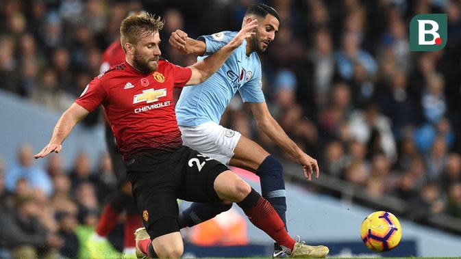 Bek Manchester United, Luke Shaw, berebut bola dengan gelandang Manchester City, Riyad Mahrez, pada laga Premier League di Stadion Etihad, Manchester, Minggu (11/11). City menang 3-1 atas MU. (AFP/Oli Scarff)