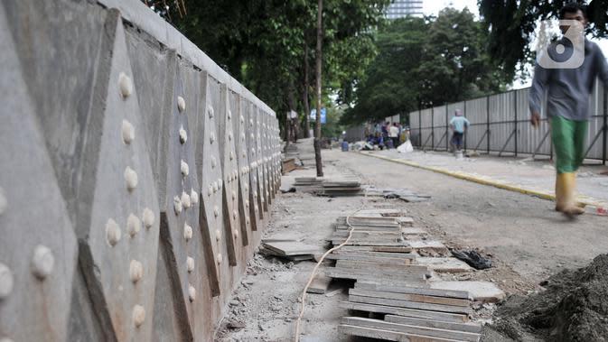 Pekerja Dinas SDA menyelesaikan proyek revitalisasi trotoar di Jalan RM Margono Djojohadikoesoemo, Jakarta, Kamis (16/1/2020). Trotoar di sisi selatan Kanal Banjir Barat itu akan dilengkapi taman dan deck view untuk melihat pemandangan Kali Ciliwung dan gedung perkantoran (merdeka.com/Iqbal Nugroho)