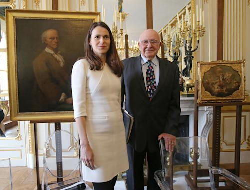 France's Culture Minister Aurelie Filippetti, and American Thomas Selldorff, right, pose for the media during a ceremony at the Culture Ministry in Paris, France, Tuesday, March 19, 2013, to return seven paintings taken from their Jewish owners during World War II, as part of ongoing efforts to give back hundreds of looted artworks that still hang in the Louvre and other French museums. Selldorff reclaimed six German and Italian paintings that his grandfather, Richard Neumann, was forced to sell during World War II to flee Nazi occupation, and another painting was returned to other recipients. In the background painting left, Alessandro Longhi(Venice, 1733 - Venice, 1813), Portrait of Bartolemeo Ferracina and painting right, Franz Xaver Karl Palko(Breslau, 1724 - Prague, 1770), Apotheosis of Saint John Nepocucene. (AP Photo/Michel Euler)