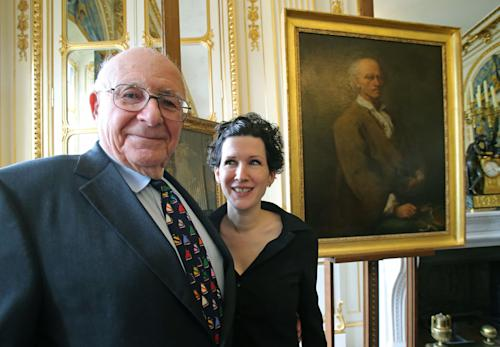 American Thomas Selldorff, left, and Austrian art historian, Sophie Lillie, who helped him to identify the painting, pose for the media during a ceremony at the Culture Ministry in Paris, France, Tuesday, March 19, 2013, to return seven paintings taken from their Jewish owners during World War II, as part of ongoing efforts to give back hundreds of looted artworks that still hang in the Louvre and other French museums. Selldorff reclaimed six German and Italian paintings that his grandfather, Richard Neumann, was forced to sell during World War II to flee Nazi occupation, and another painting was returned to other recipients. Painting in the background, Alessandro Longhi(Venice, 1733 - Venice, 1813), Portrait of Bartolemeo Ferracina. (AP Photo/Michel Euler)
