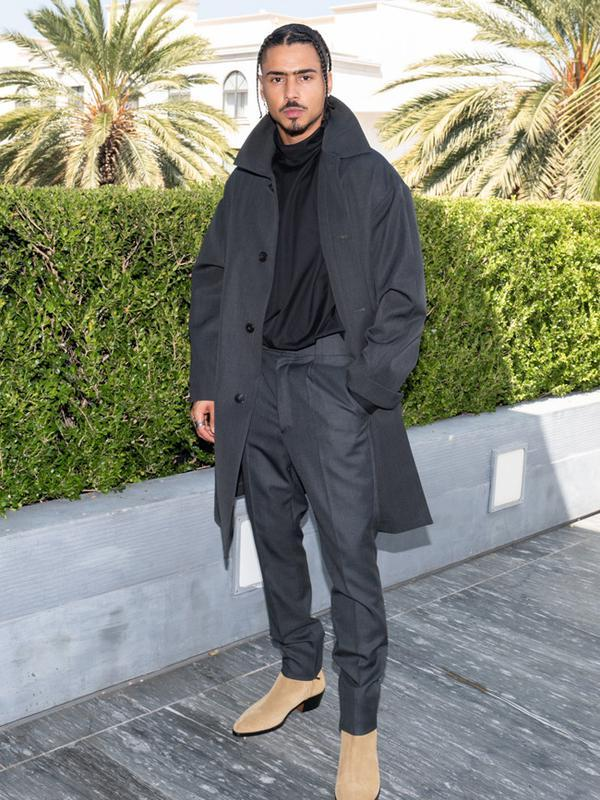 Quincy begitu tampan dengan trench dan plated trouser berbahan wool yang berwarna abu-abu. Ia memadukannya dengan high-neck collar shirt berbahan katun. Namun, penampilannya jadi berwarna dengan suede boots berwarna cream. (FOTO:Owen Kolasinski/BFA.com)