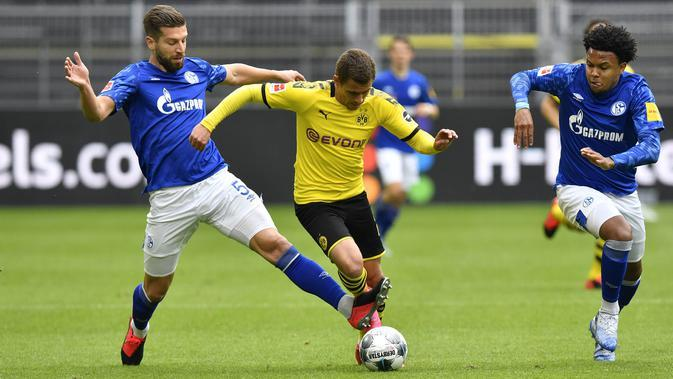 Pemain Borussia Dortmund, Thorgan Hazard, berusaha melewati pemain Schalke 04 pada laga Bundesliga di Stadion Signal Iduna Park, Sabtu (16/5/2020). Dortmund menang 4-0 atas Schalke 04. (AP/Martin Meissner)