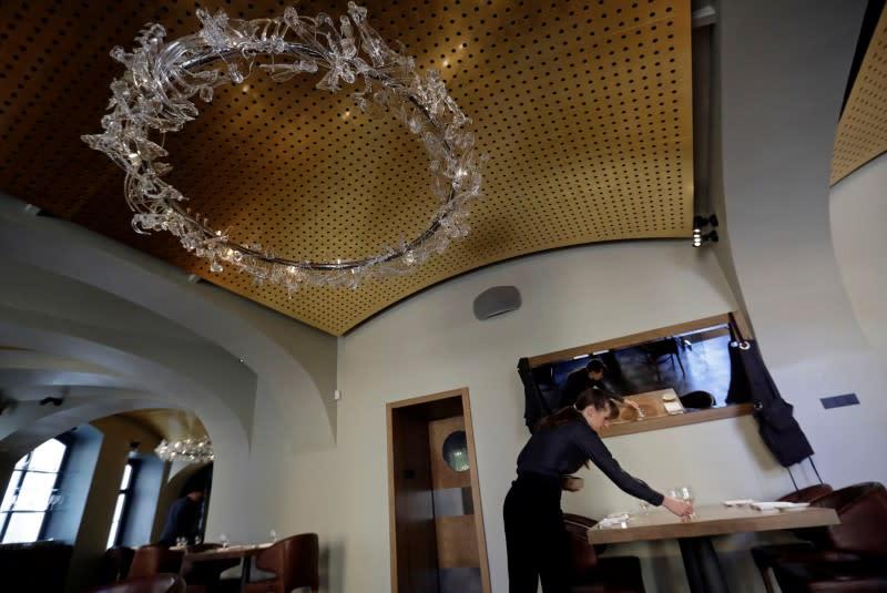 A waitress prepares a table in a restaurant in Prague