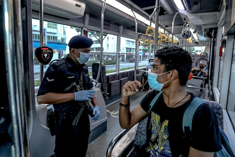 A Malaysian Armed Forces personnel conducts a routine check on bus passengers at a roadblock in Kuala Lumpur March 25, 2020. — Picture by Firdaus Latif