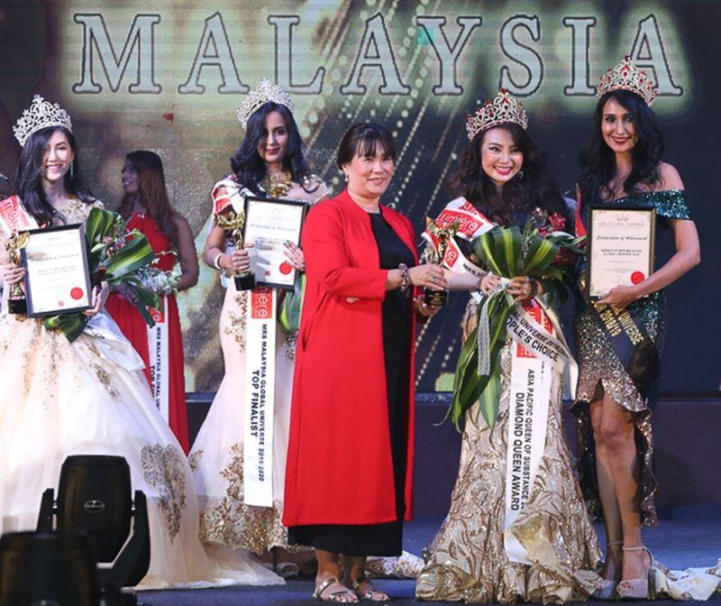 Shana Yang (second from right) receives her award from Lumiere International founder and the pageant organiser Justina Tan Quek (in red) at the pageant finale in Johor Baru. — Picture courtesy of Lumiere International