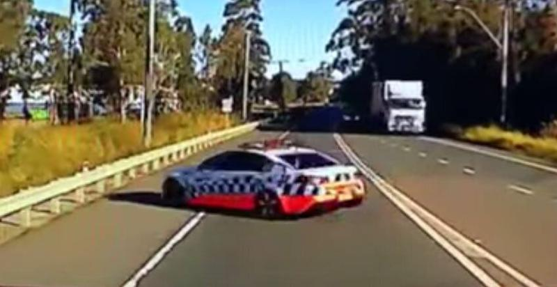 A video still of a NSW Police car turning into the path of the truck in Maitland.
