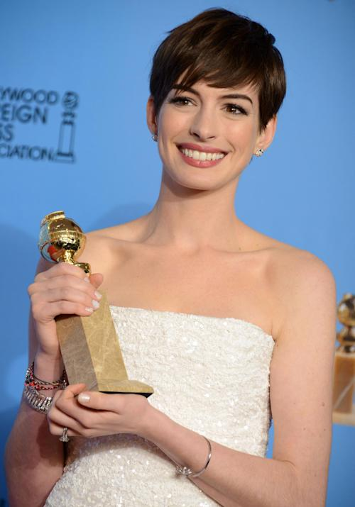 "FILE - In this Jan. 13, 2013 file photo, Anne Hathaway poses with the award for best performance by an actress in a supporting role in a motion picture in ""Les Miserables"" backstage at the 70th Annual Golden Globe Awards at the Beverly Hilton Hotel, in Beverly Hills, Calif. Actors and actresses compete separately at awards shows, a tradition some in the industry consider vital for women but others question. (Photo by Jordan Strauss/Invision/AP, File)"