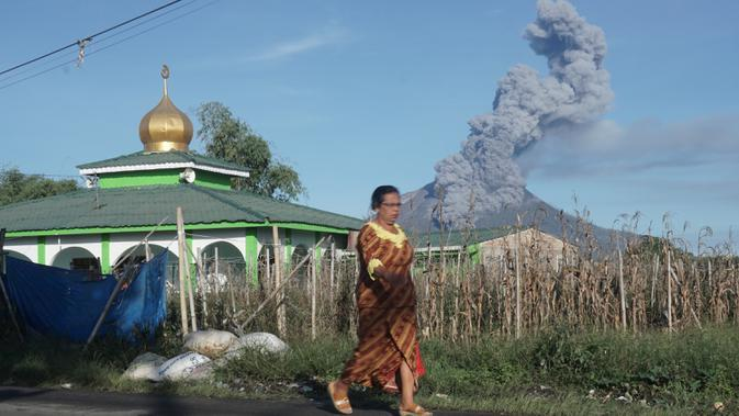 Seorang perempuan berjalan saat Gunung Sinabung mengeluarkan erupsi asap tebal ke udara di Karo, Sumatera Utara, Minggu, (23/8/2020). Untuk kesekian kalinnya Gunung Sinabung kembali erupsi dengan menyemburkan abu vulkanis ke udara hingga radius 2 kilometer. (Muhammad Zulfan Dalimunthe / AFP)