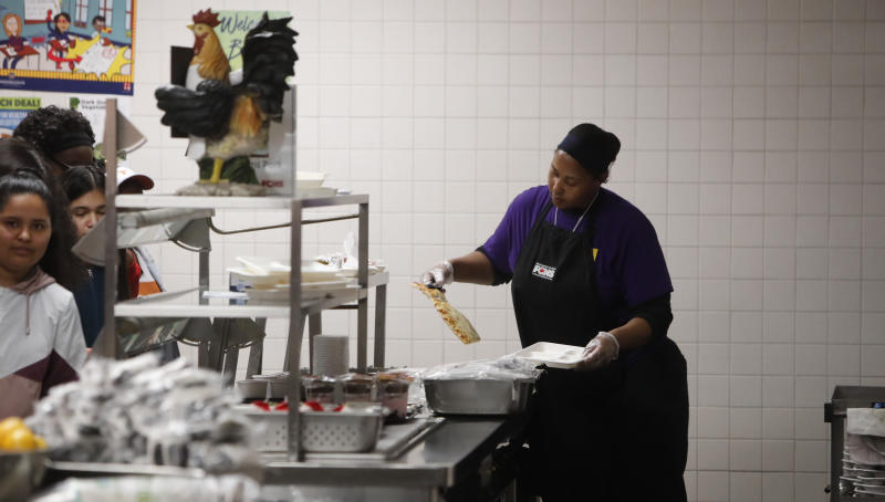 Nicole Johnson prepares lunch for students lined up in the cafeteria at Lincoln High School in Dallas, Friday, March 13, 2020. During the coming extended spring break school closures, this cafeteria and a few others in the Dallas Independent School District will be providing lunches to students despite the closure of the school. (AP Photo/LM Otero)