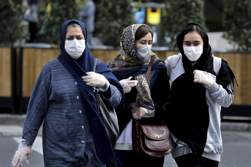 People wear masks to help guard against the Coronavirus on a street in downtown Tehran, Iran, Sunday, Feb. 23, 2020. Iran's health ministry raised Sunday the death toll from the new virus to 8 people in the country, amid concerns that clusters there, as well as in Italy and South Korea, could signal a serious new stage in its global spread. (AP Photo/Ebrahim Noroozi)