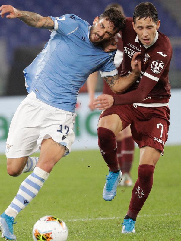 Pemain Lazio Danilo Cataldi (kiri) dan pemain Torino Sasa Lukic berebut bola saat bertanding pada laga Serie A Italia di Stadion Olimpiade Roma, Italia, Rabu (30/10/2019). Lazio membantai Torino 4-0. (AP Photo/Gregorio Borgia)