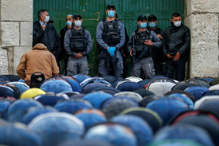 Israeli security forces wearing masks look on as Palestinian worshippers perform Eid prayers outside Al-Aqsa mosque in Jerusalem, which has been closed due to the coronavirus pandemic