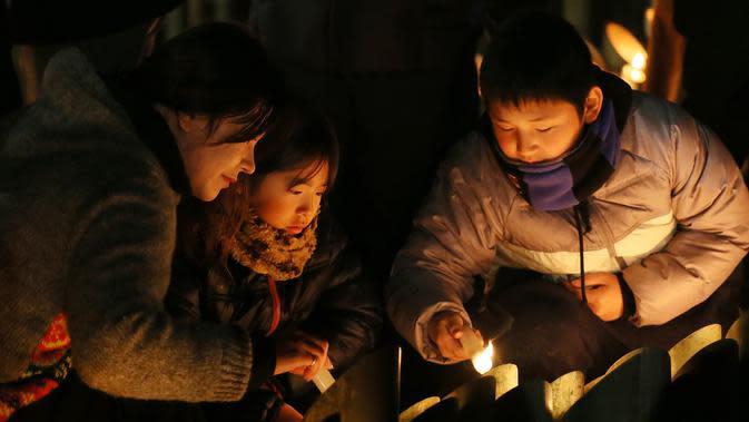 Penduduk Kobe menyalakan lilin memperingati 25 tahun gempa Hanshin Besar di sebuah taman di Kobe, Prefektur Hyogo (17/1/2020). Lebih dari 6.400 orang tewas dalam gempa bumi dahsyat yang melanda daerah Kobe pada 1995. (AFP/Jiji Press/AFP)