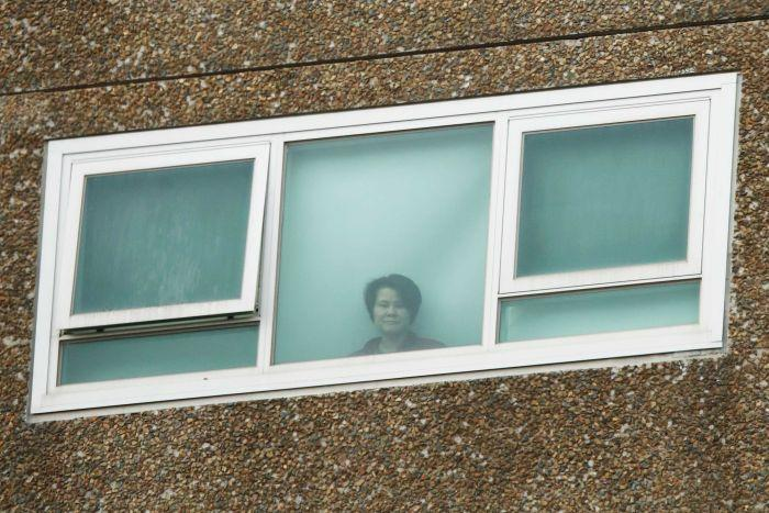 A woman looks out of a closed window in a tall brick building.