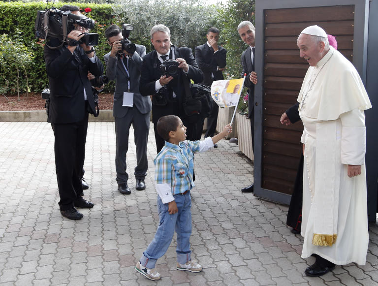 """A child waves a flag as Pope Francis arrives at Caritas residence in Assisi Friday, Oct. 4, 2013. Pope Francis made a pilgrimage Friday to the hillside town of Assisi and the tomb of his namesake, St. Francis, the 13th-century friar who renounced a wealthy, dissolute lifestyle to embrace a life of poverty and minister to the most destitute. St. Francis was famously told by God to """"repair my house."""" (AP Photo/Stefano Rellandini, Pool)"""