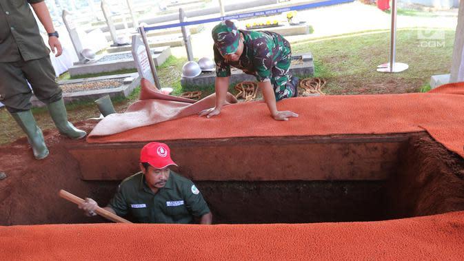 Pekerja menggali makam Presiden ke-3 RI BJ Habibie di TMP Kalibata, Jakarta, Kamis (12/9/2019). Habibie bakal dimakamkan di TMP Kalibata hari ini. (Liputan6.com/Herman Zakharia)