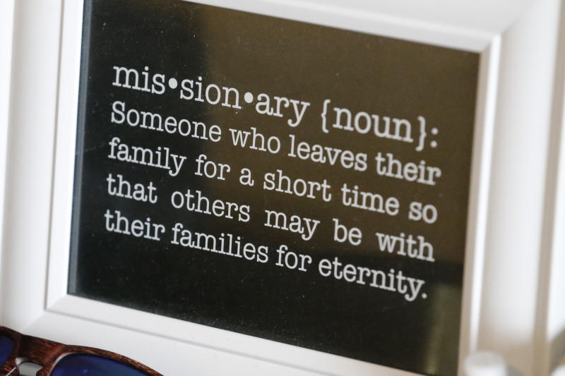 In this May 27, 2020, photo, a framed definition of missionary sits on a desk at the apartment of missionaries with The Church of Jesus Christ of Latter-day Saints, in Brigham City, Utah. After hastily bringing home 26,000 young men and women who were serving in foreign countries, the faith has begun sending many of them out again in their home countries with a new focus on online work that could stick even when the pandemic is over, church officials told The Associated Press. (AP Photo/Rick Bowmer)