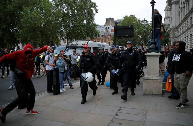 Protestors watch as police officers carrying riot helmets walk along the street near Parliament Square during an anti-racism demonstration in London after George Floyd, an unarmed black man, died in police custody Minneapolis, USA