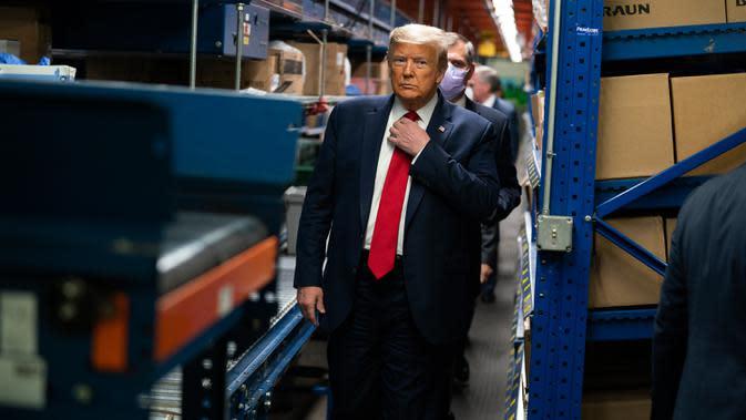 Presiden AS Donald Trump merapikan dasinya saat mengunjungi Owens & Minor Inc., sebuah perusahaan pemasok peralatan medis di Allentown, Pennsylvania, Kamis (14/5/2020). Penampilan Trump saat melakukan kunjungan tanpa mengenakan masker menjadi sorotan di tengah pandemi Covid-19. (AP Photo/Evan Vucci)
