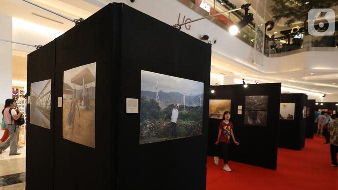 Pengunjung melihat pameran foto Membangun Indonesia di Mall Neo Soho, Jakarta, Minggu (10/11/2019). Pameran menampilkan foto-foto jurnalistik mengenai pembangunan Indonesia yang dikerjakan Jokowi-JK selama 5 tahun bekerja dan akan berlangsung hingga 17/11. (Liputan6.com/Angga Yuniar)
