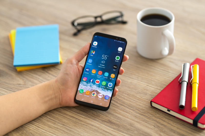 Hand holding a smart phone on a wooden desk. The smart phone is an Samsung Galaxy S9 plus. Samsung Galaxy is a touchscreen smart phone produced by Samsung Electronics.