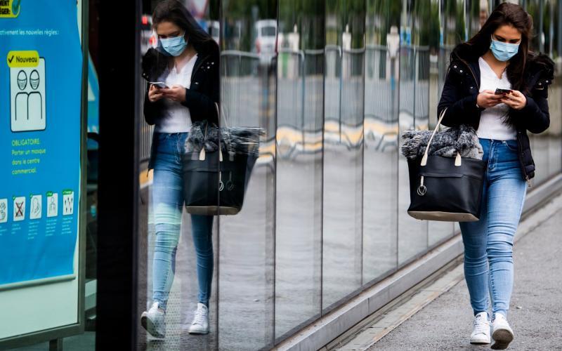 A woman wearing a protective mask in Fribourg, Switzerland, - Jean-Christophe Bott/Keystone via AP