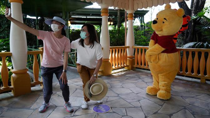 Pengunjung yang mengenakan masker berswafoto dengan karakter kartun Winnie the Pooh di Disneyland Hong Kong pada Jumat (25/9/2020). Setelah dibuka dan tutup kembali, Disneyland Hong Kong dibuka kembali untuk wisatawan. (AP Photo/Kin Cheung)