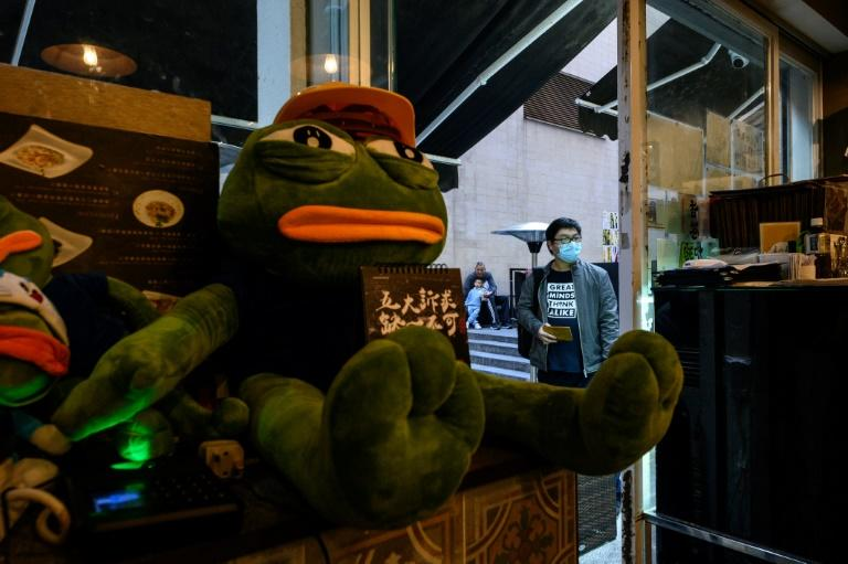 Diners slurp wonton under the watchful gaze of a gas mask-wearing Pepe the Frog, which has become a mascot of the pro-democracy movement