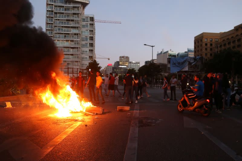 Demonstrators set fire during a protest against the collapsing Lebanese pound currency and the price hikes in Beirut