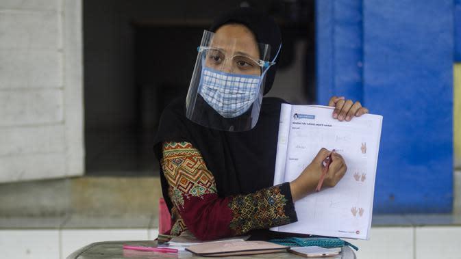 Guru mengenakan masker saat mengajar siswa SD secara tatap muka di Sekolah Islam Ibnu Aqil Ibnu Sina, Soreang, Bandung, Jawa Barat, Rabu (5/8/2020). Indonesia akan mengizinkan sekolah di zona hijau COVID-19 melakukan pembelajaran tatap muka di bawah protokol kesehatan yang ketat. (Xinhua/Septianjar)