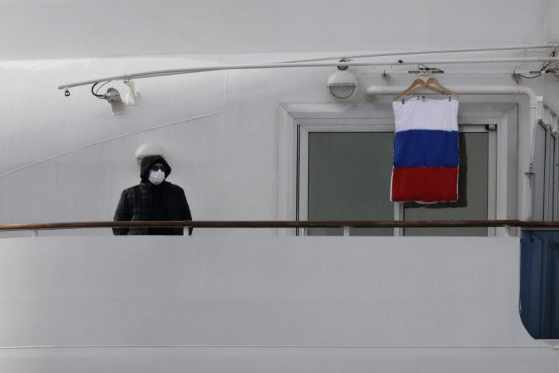A quarantined passenger on the Diamond Princess cruise ship stands on the balcony of his cabin next to a Russian flag Saturday, Feb. 15, 2020, in Yokohama, near Tokyo. A viral outbreak that began in China has infected more than 67,000 people globally. The World Health Organization has named the illness COVID-19, referring to its origin late last year and the coronavirus that causes it. (AP Photo/Jae C. Hong)