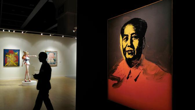 Pengunjung berjalan di samping lukisan Zedong karya seniman Andy Warhol di Sotheby's Modern and Contemporary Art Evening Sale, Hongkong, Jumat (31/3). Lukisan ini diharapkan bisa laku seharga USD 15 juta (sekitar Rp 200 miliar). (AP Photo / Vincent Yu)