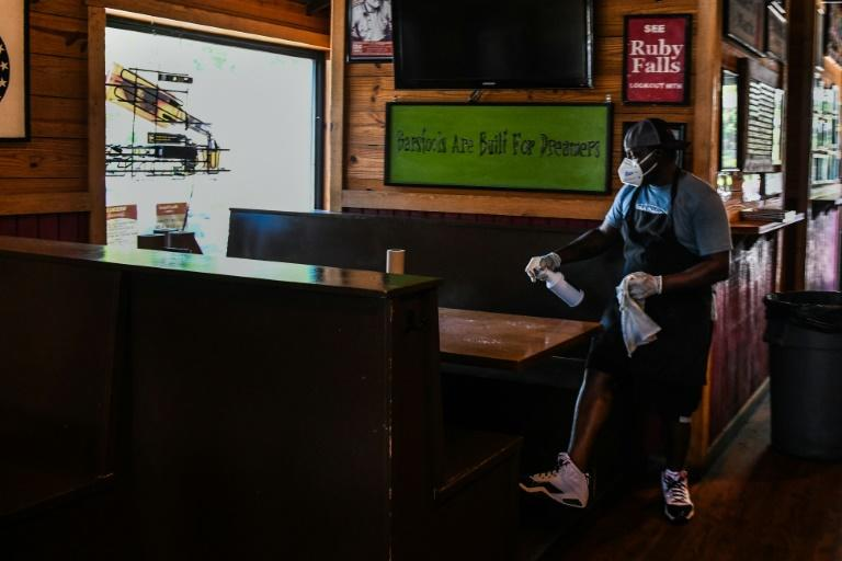 Restaurant employees in Georgia must wear masks at work -- here, an employee of Moe's Original BBQ restaurant in Atlanta cleans off a table