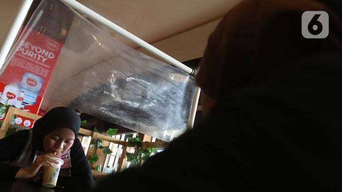 Pengunjung minum di sela-sela pembatas plastik di salah satu restoran Mall Bekasi, Jawa Barat, Minggu (7/6/2020). Sejumlah tempat makan mulai menerapkan protokol kesehatan untuk pengunjung yang makan ditempat untuk mencegah penyebaran wabah COVID-19. (Liputan6.com/Herman Zakharia)