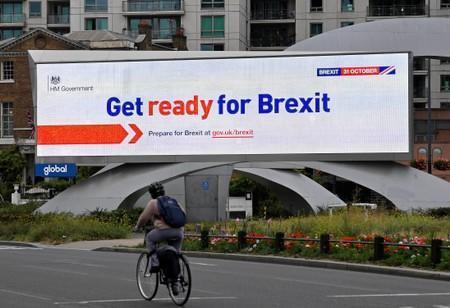 A cyclist rides past an electronic billboard displaying a British government Brexit information awareness campaign advertisement in London, Britain