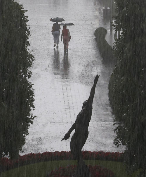 Tennis fans exit the Billie Jean King National Tennis Center as a heavy rain falls suspending play of the 2014 U.S. Open tennis tournament, Sunday, Aug. 31, 2014, in New York. (AP Photo/Kathy Willens)